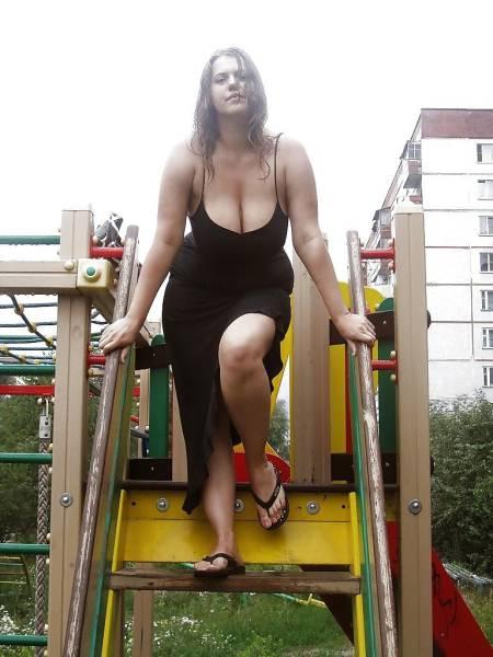 Девушка с натуральной грудью 6-го размера в черном платье с большим декольте