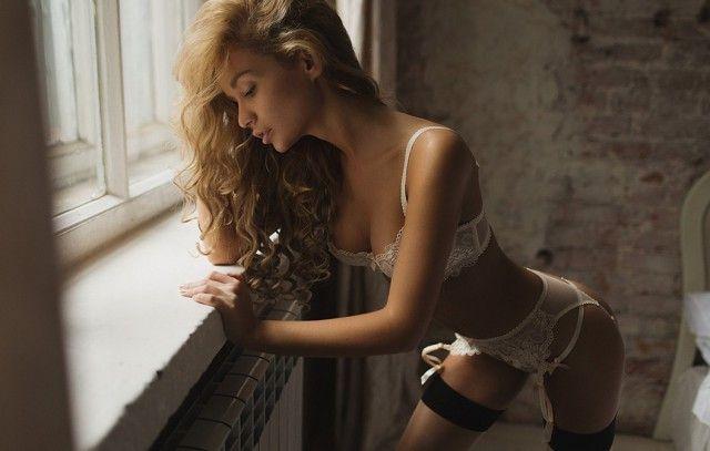 Сексуальная красотка в черно-белом нижнем белье стоит у окна
