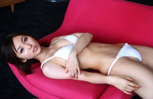Красивая азиаточка со стройной фигурой в белом белье лежит на красном диване
