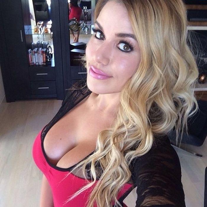 Селфи блондинки в большой грудью в красно-черном платье дома