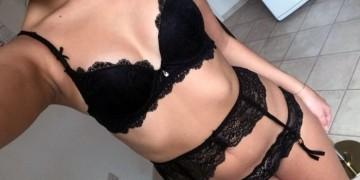 Селфи девушки в черном кружевном нижнем белье с поясом для чулков