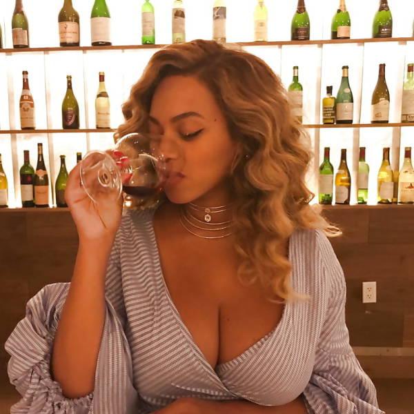 Девушка с большой красивой грудью 4-го размера пьет в баре коктейль