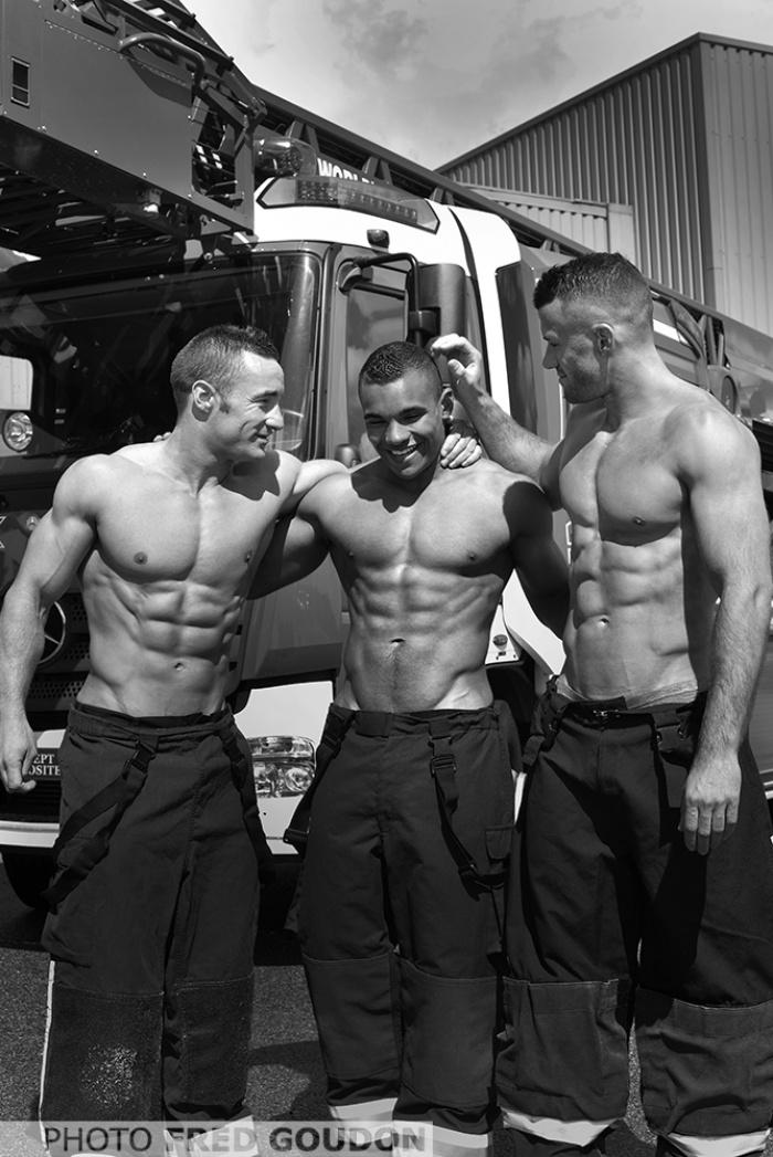 Три голых по пояс накачанных с крепкими мышцами мужчины стоят в обнимку