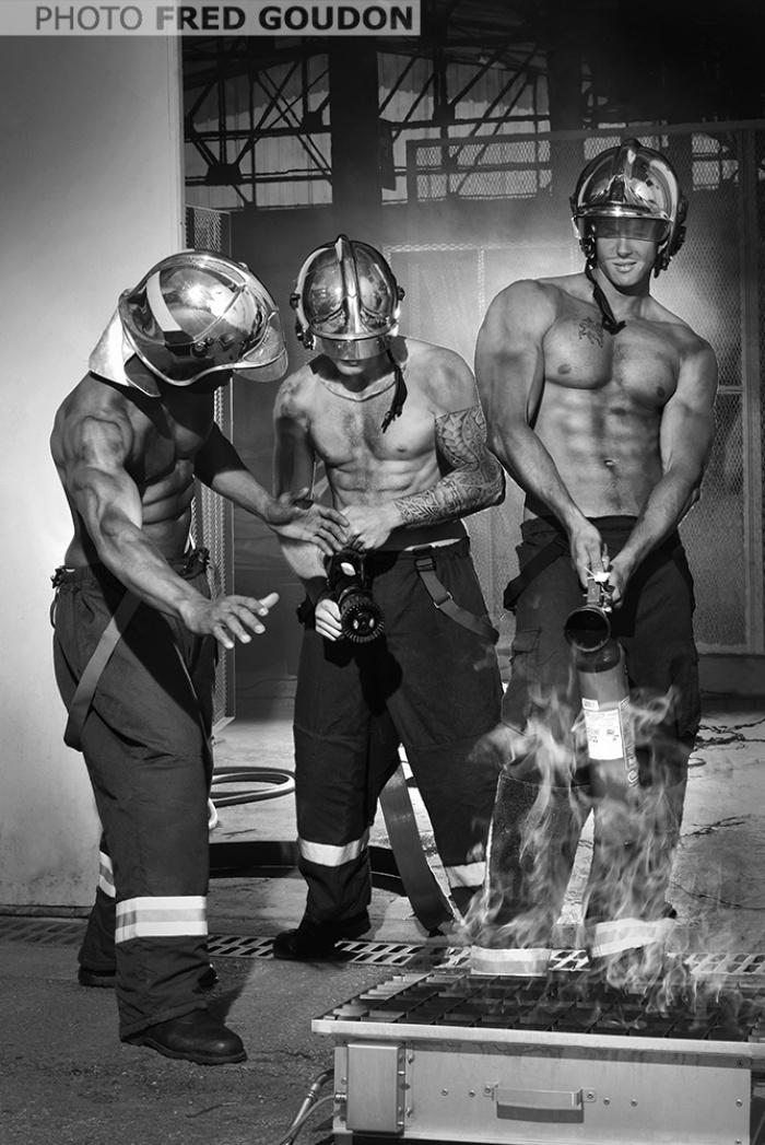 Три голых по пояс накачанных мужчины в шлемах тушат пожар