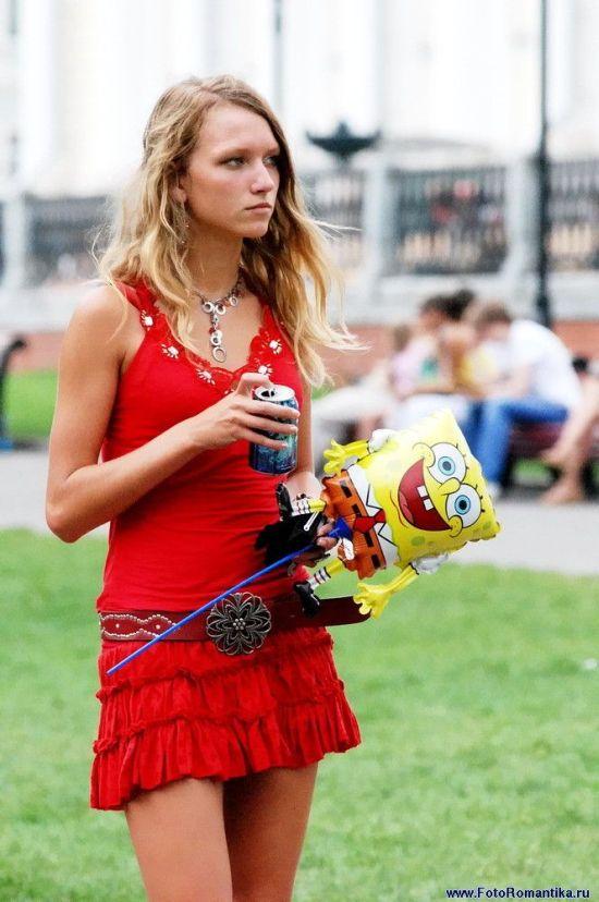 Девушка-мечта в красном коротком платье со стройными ножками и красивой грудью
