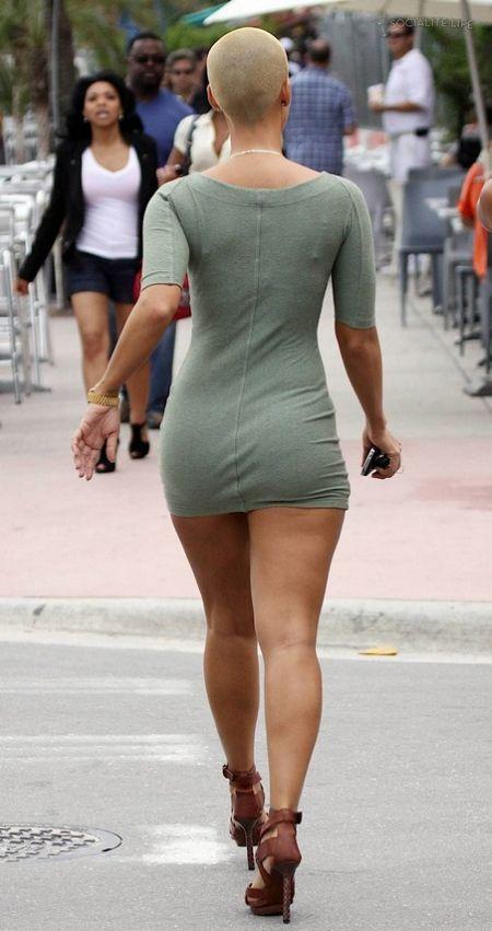 Лысая красотка с охренительной фигурой, длинными ногами и большой грудью без лифчика в коротком платье видом сзади