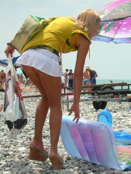 Девушка на пляже засвечивает свою красивую попку под коротенькой белой юбкой