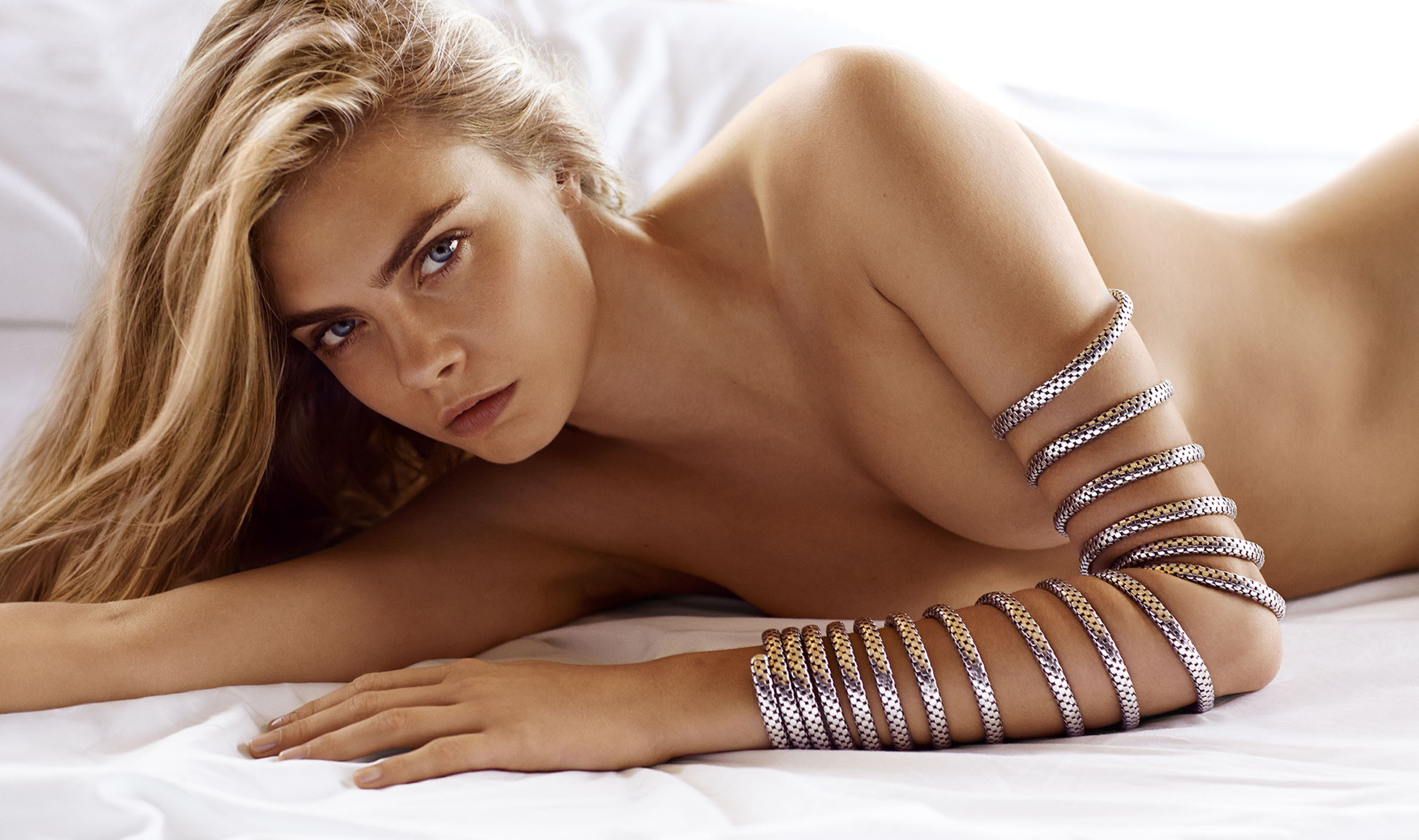 Голая Кара Делевинь позирует лежа с браслетами на руке