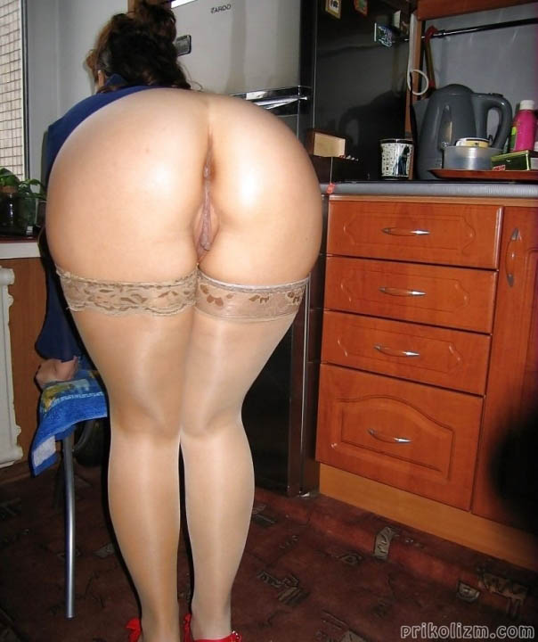 Девушка в кружевных чулках и без трусов стоит раком дома на кухне
