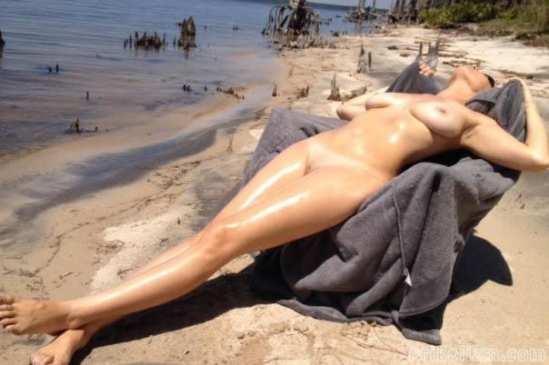 Красотка лежит голой на пляже