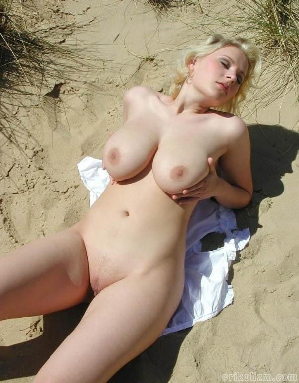 Голая блондинка ласкает свои груди лежа на песке