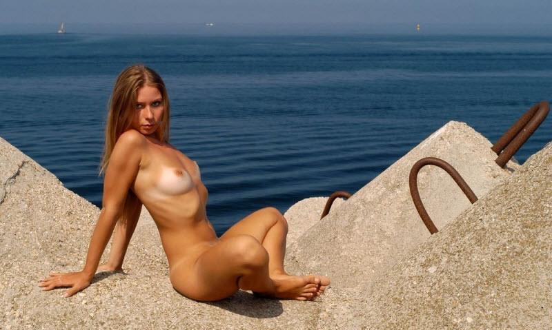 Голая прелестная девчонка сидит на камнях причала возле моря