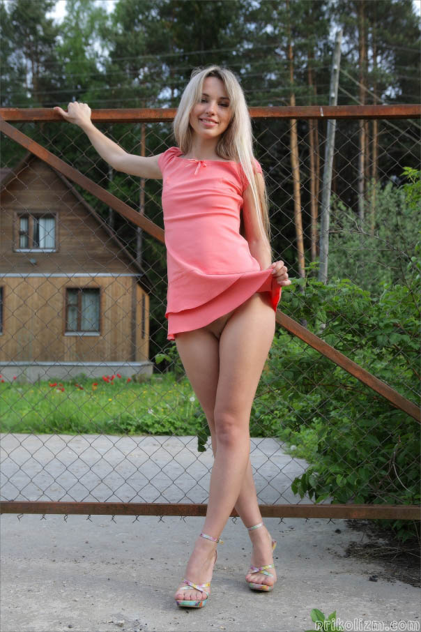 Стройная блондинка с длинными ногами в розовом платье на голое тело