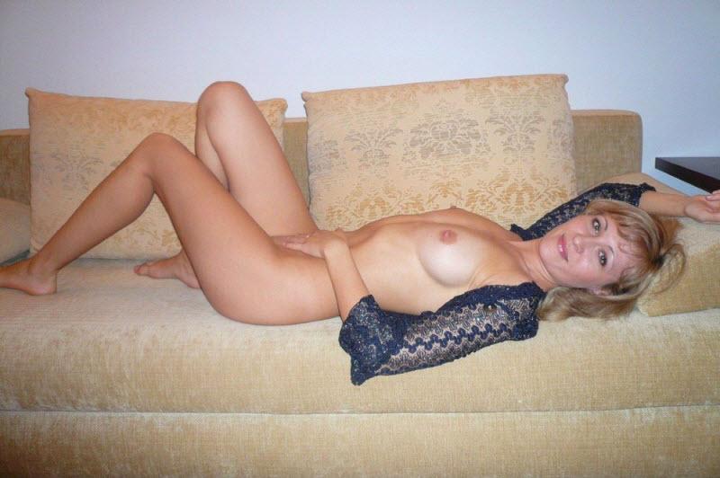 Голая женщина с большими прелестями позирует на диване дома