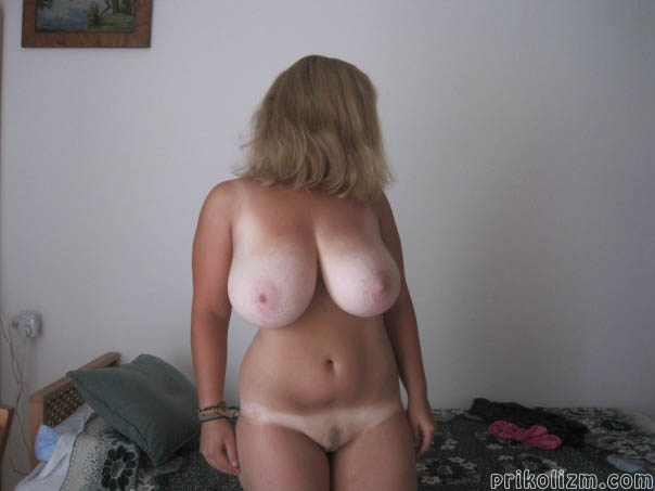 Голая женщина с белыми сиськами сидит на кровати в своем доме