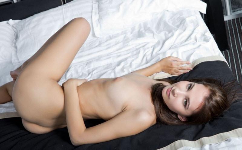 Красивая голая брюнетка со стройной фигурой и тонкой талией позирует на кровати