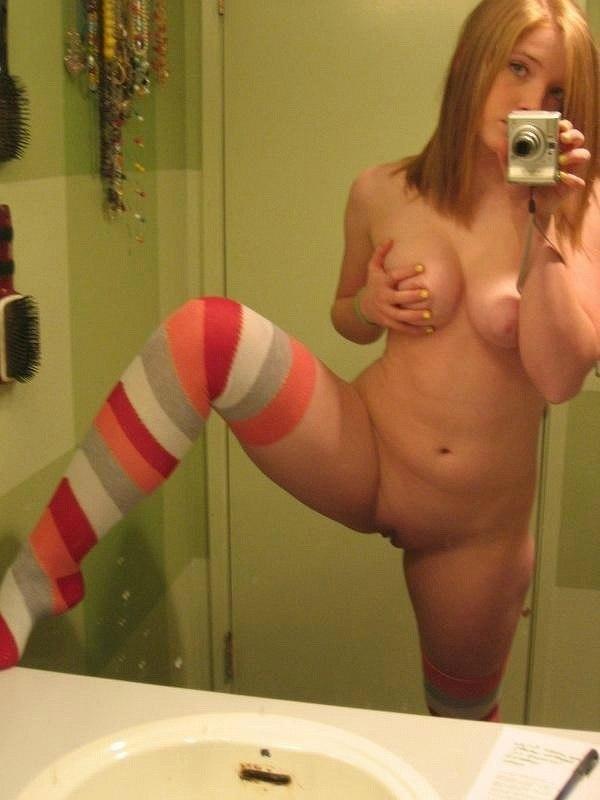 Голая блондинка задрала ногу в ванной комнате