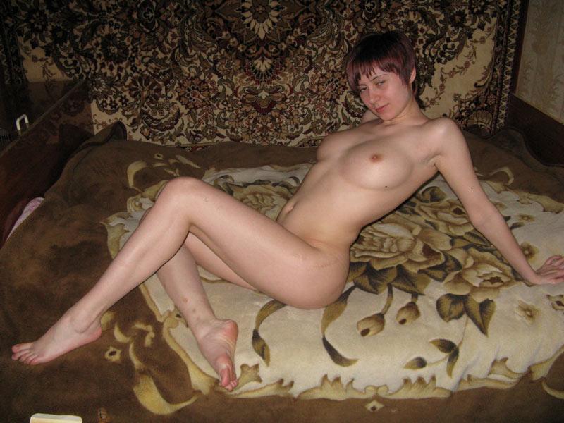 Русская жена на фоне домашнего ковра возле кровати