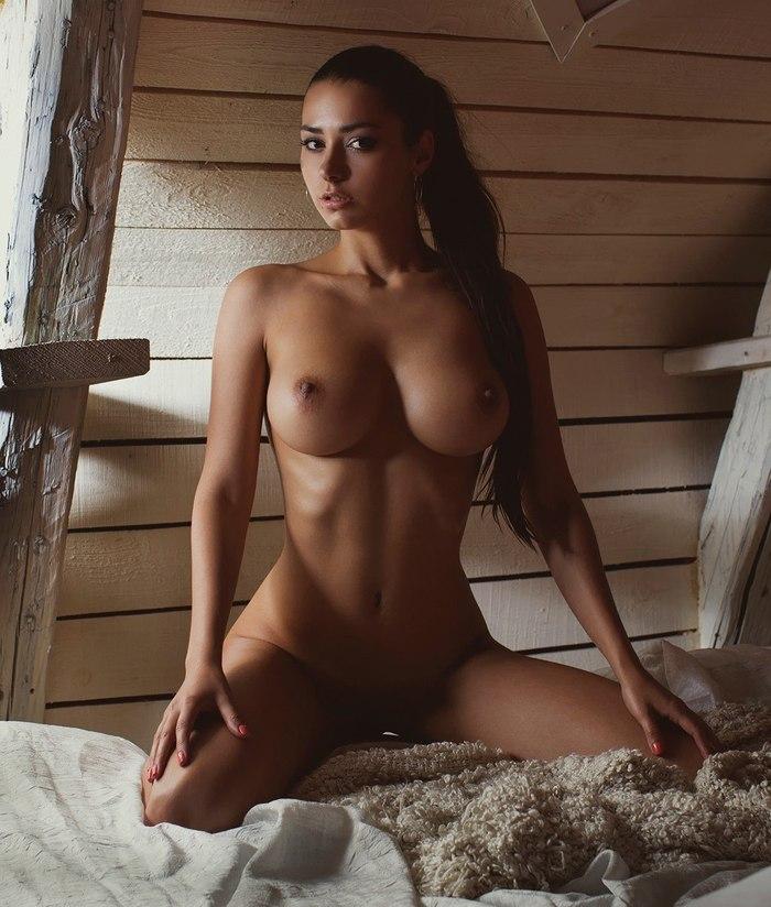 Девушка с красивой фигурой сидит раздвинув ноги