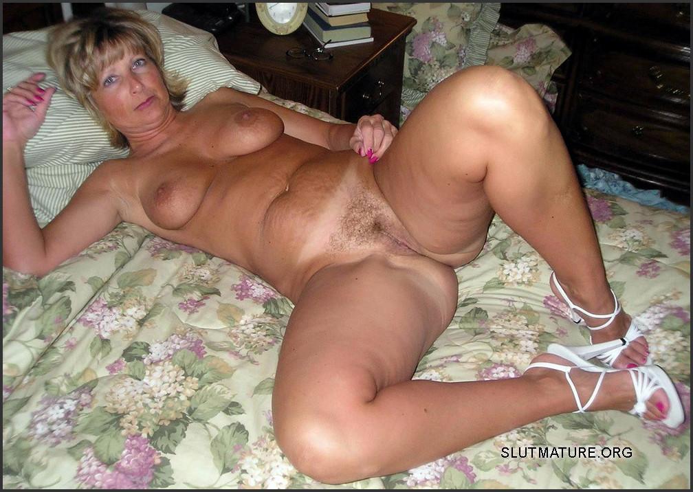 Голая женщина в зрелом возрасте на кровати