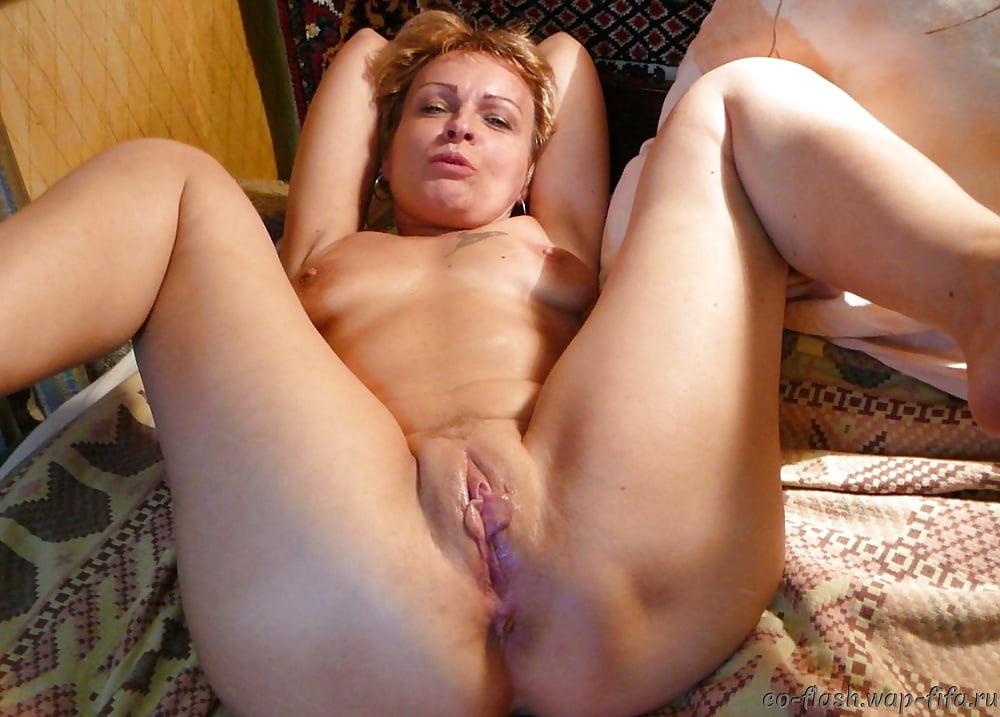 Голая женщина пошло разложилась на кровати показывая свою пизду