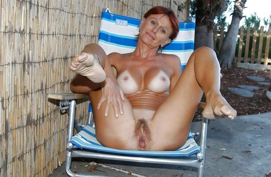 Загорелая женщина в зрелом возрасте на лежаке