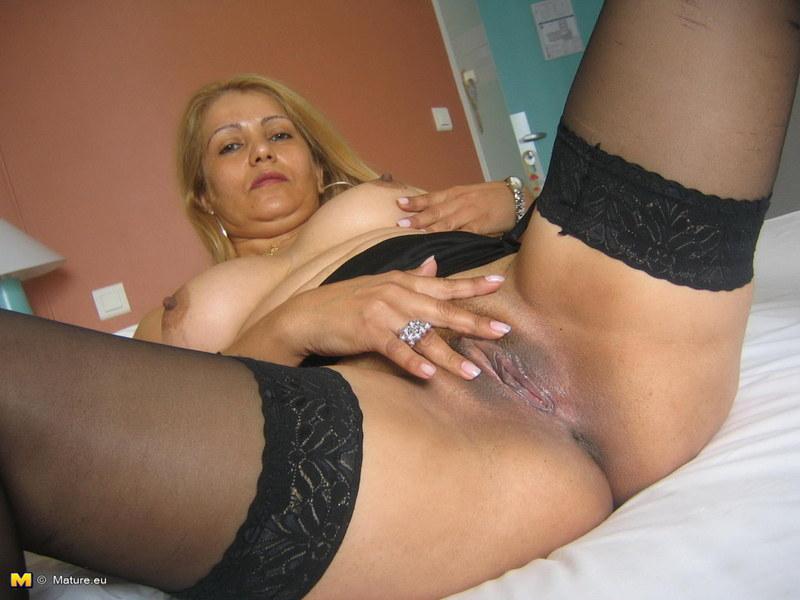 Красивая женщина в черных чулках на частном фото ласкает себя