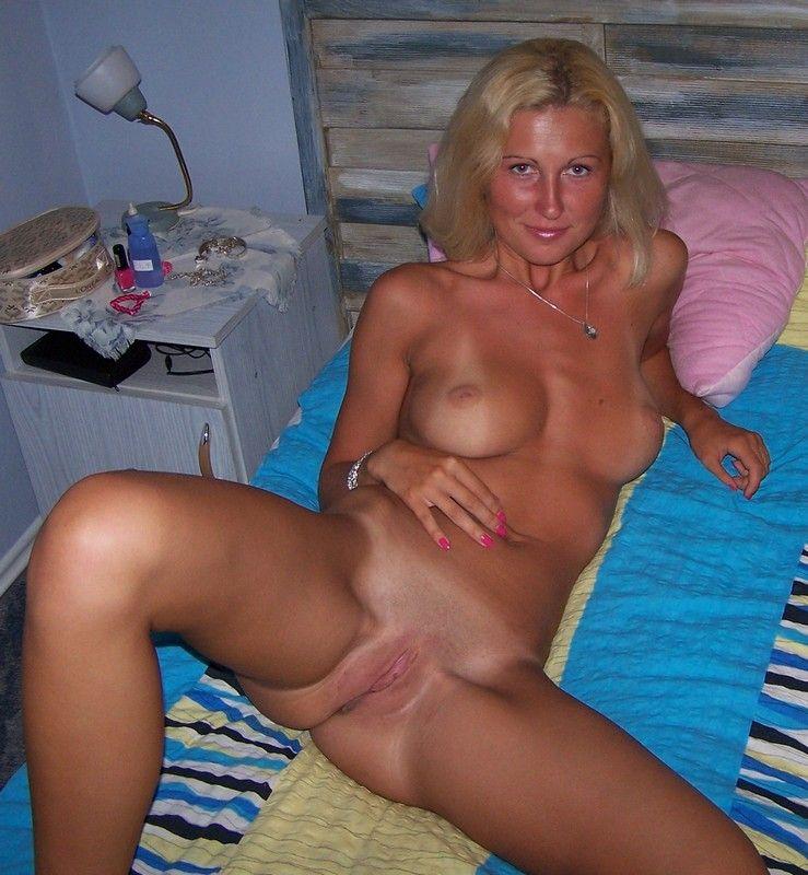 Женщина со светлыми волосами позирует на кровати