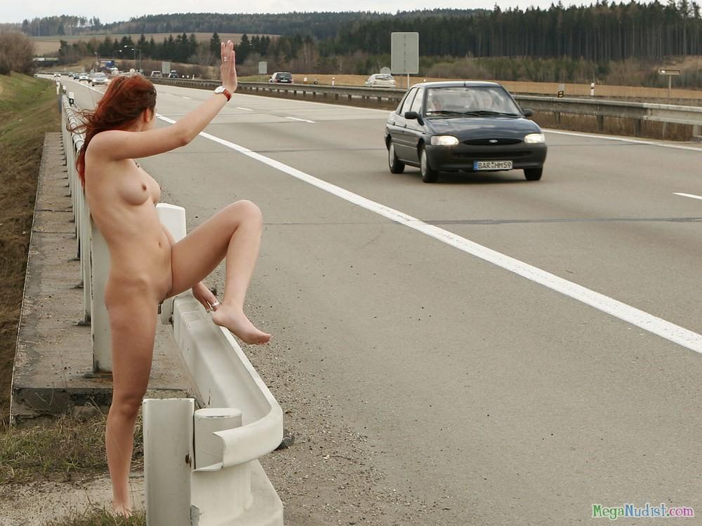 Пытается споймать попутку на трассе