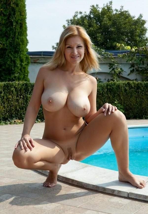 Светловолосая женщина позирует голой возле бассейна