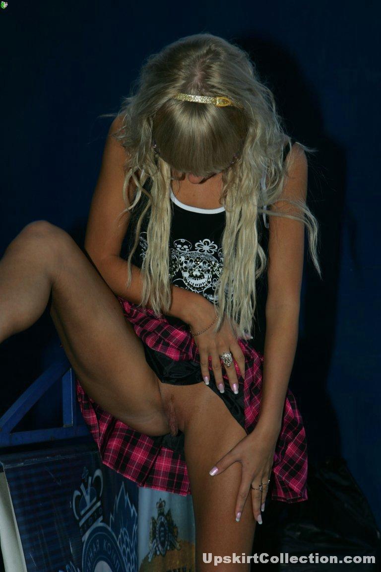 Сексуальная блондинка показывает свою пизду под клетчатой юбкой